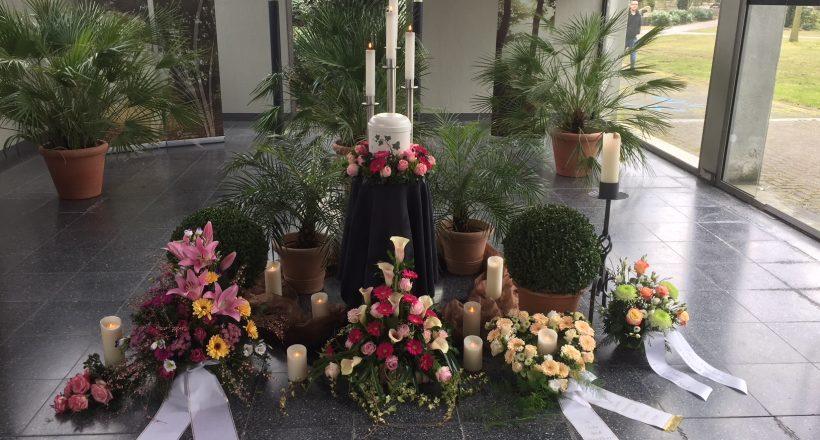 Urne mit Kerzen und Blumen